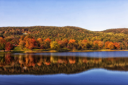 Autumn forest by mirror-shiny lake and blue sky. Photo.