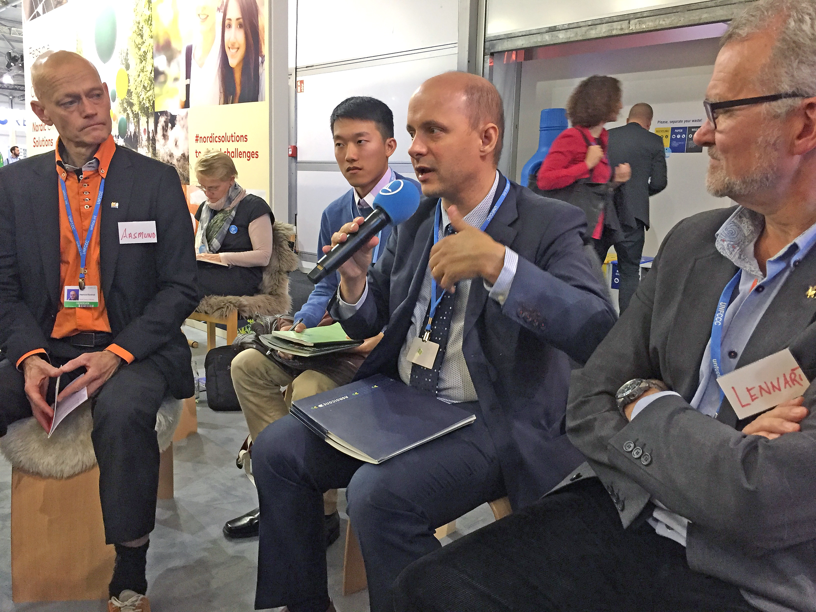 Four men in suits sitting in a row, man in center is holding a microphone. Photo.