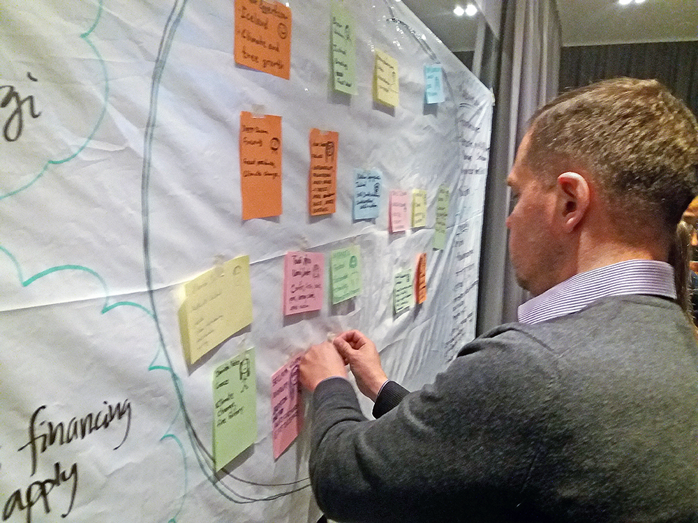 Man looking at a white board with post-it notes on it. Photo.