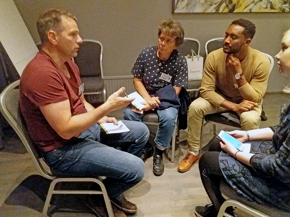 Four people sitting in circle talking. Photo.