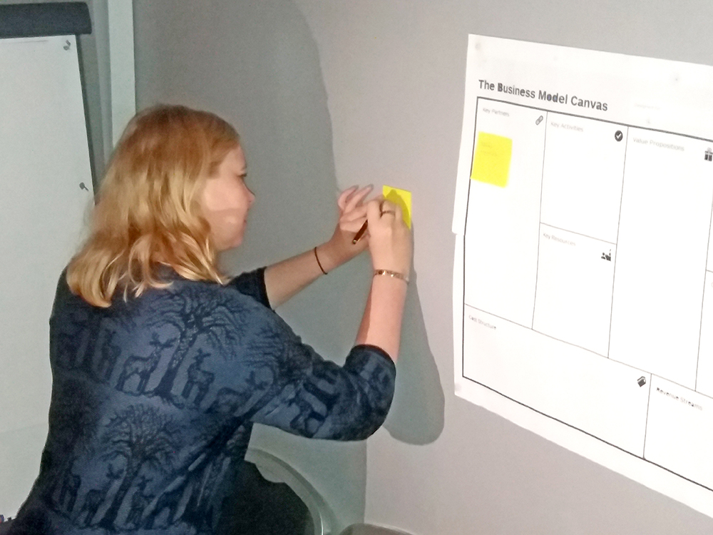 Woman standing next to white board writing on a post-it. Photo.